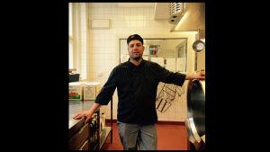 Kocken David Liebe iklädd svarta kockkläder. Står i skolköket.