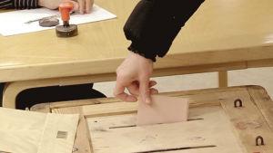 En person lägger en valsedel i valurnan.