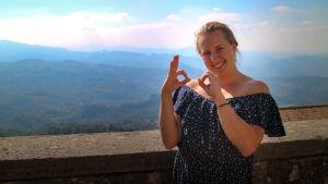 Kvinna iklädd blommig klänning. Står uppe på en borg och bakgrunden syns ett bergigt landskap. Hon visar siffrorna 6 och 0 med sina händer.