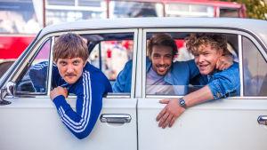 Närbild på tre, glada män som sitter i en bil.