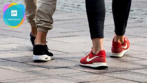 Två personer promenerar med korta byxor som lämnar vristerna bara. Yle Nyhetsskolans logo i vänstra övre hörnet.
