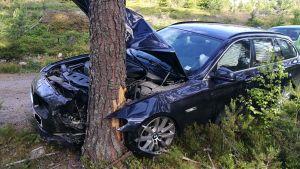 en mörkblå bmw som krockat in i ett träd och hela vänstra framsidan skotades.