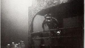 Vanha kuva sukeltajasta laivan hylyn vierellä