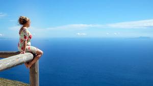 Kvinna i blommig klänning som sitter på ett staket och blickar ut över ett blått hav. Också himlen är blå.