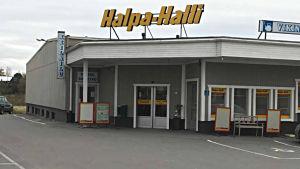 Halpa-Halli i Vörå sett rakt framifrån mot ingången. En stor skylt med logon står uppe på taket av den ganska låga butikslokalen från 70-talet.