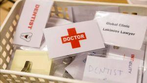 "Låda med titelskyltar, t.ex. ""Dentist"" och ""Global clinic lakimies lawyer""."