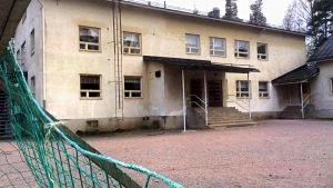 En ljus rappad 50-talsskolbyggnad i rätt dåligt skick. Svart plåttak. I förgrunden ett grönt fotbollsmålnät.