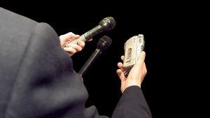 En journalist står med intervjuredskap i handen