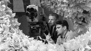 Risto Vanari ja Jukka Virtanen tv-kameran takana röyhelöisissä lavasteissa.