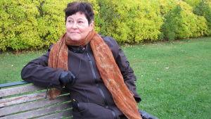 Professor Kevät Nousiainen, med mörkt kort hår och en mörk jacka, sitter på en parkbänk
