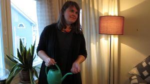 Kvinna, Sara Mikander, med långt mörkt hår står med ryggen mot fönster, vattenkanna i handen