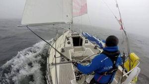 Michael Wahlroos ensam på sin segelbåt, mitt ute på havet.