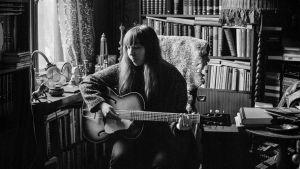Artisten Nightbird sitter med en akustisk gitarr i famnen.