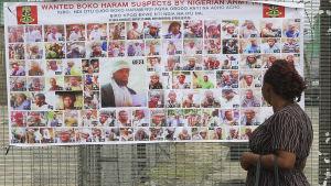 En nigeriansk kvinna tittar på en plansch med bilder på misstänkta boko haram-medlemmar.