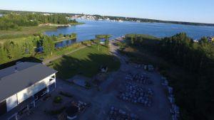 En byggnad och en gårdsplan vid havet fotograferade uppifrån.