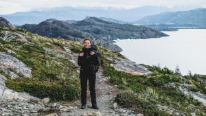 En kvinna iklädd svarta vandringskläder, står på en stig. Bakom henne syns berg. Hon har en stor ryggsäck på ryggen.