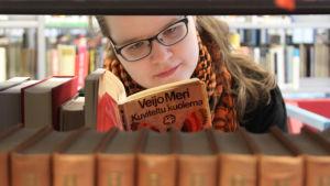Kirjabloggari Niina Tolonen lukee kirjahyllyjen välissä Veijo Meren teosta.
