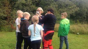 Lärare och elever vid Katarinaskolan studerar vattndjur vid Pumpviken i Karis.