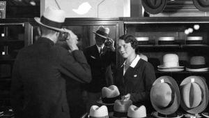 Kundbetjäning på hattavdelningen år 1930. Man köper hatt av kassabiträde i Stockmann.