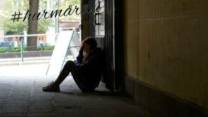 Tonårsflicka sitter på marken i portgång