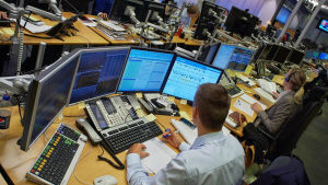 Dealer framför sina skärmar i Svenska Handelsbankens dealingrum