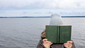 Luettua elämää -blogistin kuva Juhani Ahon kirjaa lukemassa
