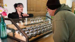 Mies katselee tuotteita vitriinissä, naismyyjä esittelee