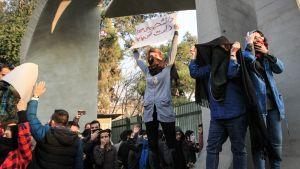 Naamioituneita opiskelijoita banderolleineen