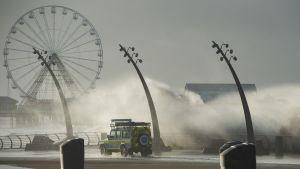 Valvontaviranomaisen maastoauto ajaa rantatiellä. Suuria tyrskyjä lyö rantaan heittäen vettä auton päälle. Taustalla näkyy maailmanpyörä.