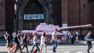 Vaaleanpunainen panssarivaunu ja ohi käveleviä ihmisiä.