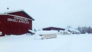 Hyrynsalmen sirkkeli ja höylä oy:n rakennus lumisessa maisemassa.