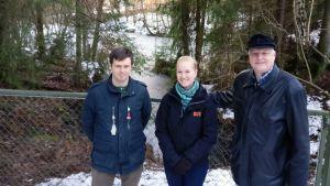 Metsittyneen kaivannon edessä seisovat arkeologi Andreas Koivisto sekä Linnaisten omakotiyhdistyksestä Minttu Lukkala ja Jukka Mäkinen.  Kuvassa näkyy myös kaivonnon ympäröivä verkkoaita. Vedellä täyttynyt kaivanto, joka on jäässä.