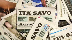 Sanomalehtiä levitettynä pöydälle.