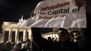 """Mies kantaa julistetta, jossa lukee englanniksi """"Jerusalem on Palestiinan pääkaupunki""""."""