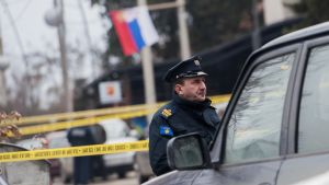Poliiai seisoo eristysnauhan edessä poliisiauton vieressä.