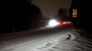 Lumisessa tiessä näkyy auton jäljet, kauempana vilkkuu hälytysajoneuvojen valoja. Ympärillä on pimeää.
