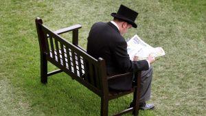 Yksinäinen mies istuu penkillä.