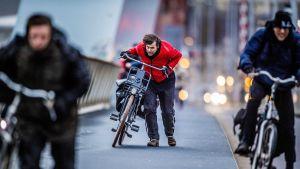 Ihmiset työntävät pyöriään erittäin kovassa vastatuulessa.