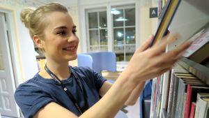 Nuori nainen laittaa hymyssä suin kirjaa kirjahyllyyn kirjastossa.