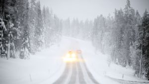 Autoja lumipyryssä maantiellä.