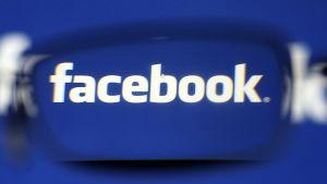 Facebookin logo kuvattuna linssin läpi.