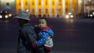 Mies kantaa lasta Pjongjangissa Pohjois-Korea.