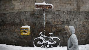 Jalankulkija lumisateessa Montmartrella.