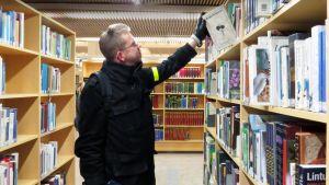 Mies poimii kirjahyllyn ylähyllyltä kirjan.