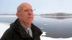 Mies seisoo talvimaiseman edessä ja katsoo kohti taivasta.