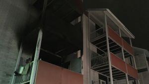 Palaneen kerrostalon julkisivu, parveke ja seinä mustana.