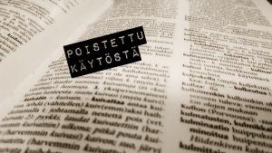 Henkilön kädessä olevan sanakirjan päälle on lisätty käytöstä poistettu -grafiikka.