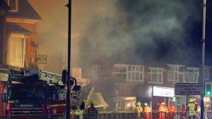 Kuvassa sammuttajat tarkastelevat savun keskellä räjähdyksen aiheuttamia tuhoja.