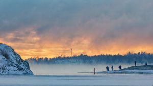 Ihmiset ihailemassa auringonlaskua ja merisumua Helsingissä.