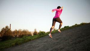 Nainen juoksee ylämäkeä.